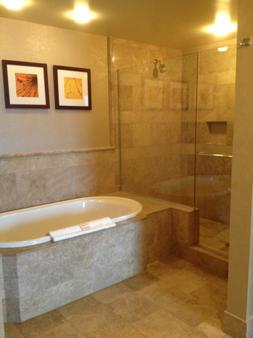 Both the bathtub and shower areas are large and lined in marble and stone tiled.