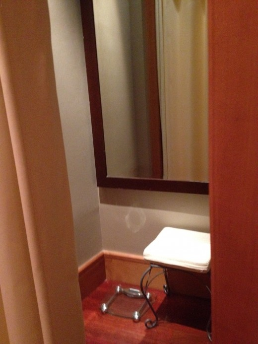 A dressing room is supplied with mirror, bench and weight scale.