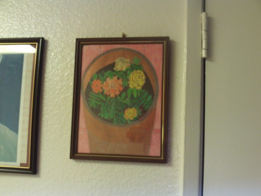The framed marigold drawing hanging on the wall.