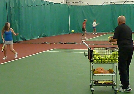 USPTA Teaching Pro Bill Graves feeds balls to young player, Megan, during a lesson.
