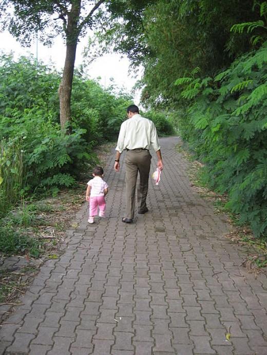 A dad walking his daughter down a brick path