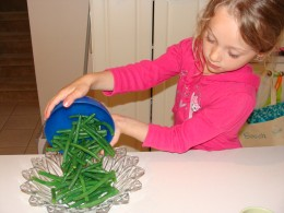 Grace adds the green beans to a bowl.