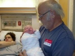 Papa holding his grandson for the first time