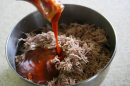Pour the BBQ sauce into the shredded meat mixture.