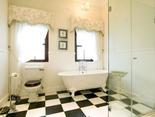 Victorian style bathroom featuring a checkered floor, glass shower, and vintage bath tub.