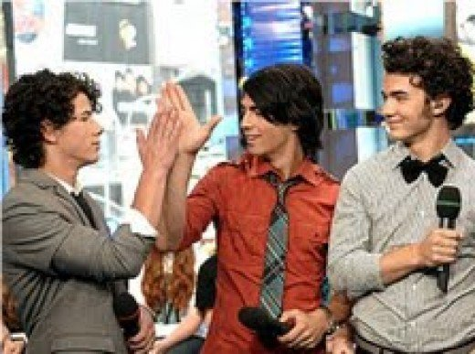 """by Lines,Vines and Trying Times;           """"Nick and Joe look like they missed              the high five the first time and Kevin              is just like 'ahhh....there ya go!"""""""