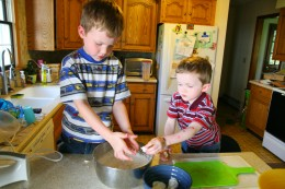 Both boys crush meringue cookies and add them to the cream.