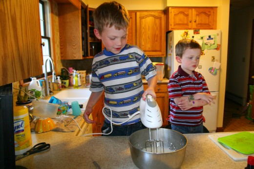 A little chef is a little upset that he has to take turns with the electric mixer.