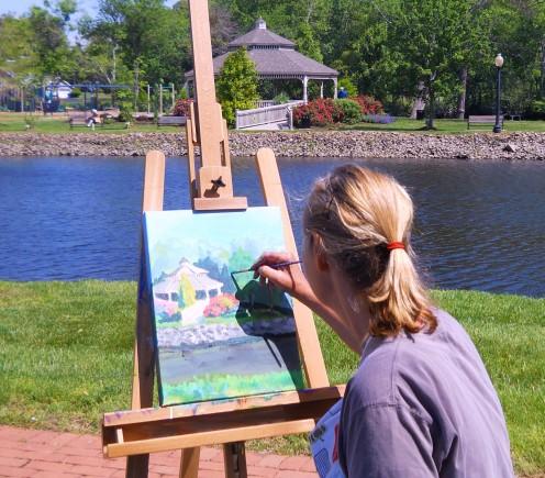 Deborah McClure painting the picnic gazebo in Milton Memorial Park.
