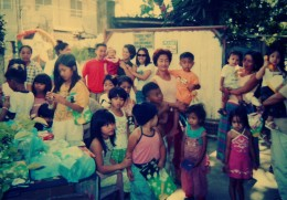 """Neighbourhood kids along with their mothers waiting for """"Little Santa"""" to hand out the gifts some wrapped in Christmas wrapping and some ready in plastic bags."""