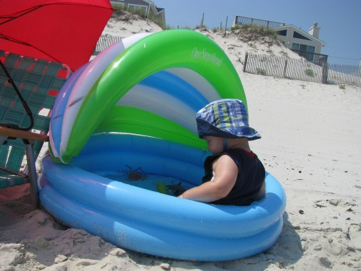 Keep your kids safe in the sun. Wearing a hat and staying in the shade are two ways to avoid sunburn.