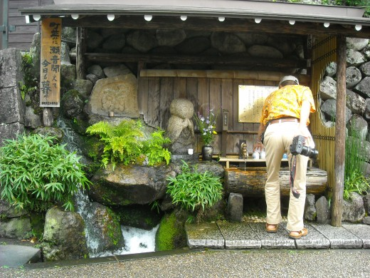 A man samples the fresh and clean holy water of Gujo City.