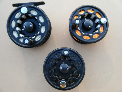 A fly reel with a floating line (light green), spare spool with partially sinking line (orange), and an empty spool.
