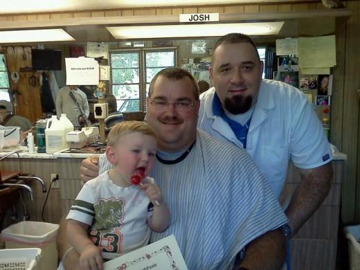 Happy little boy enjoying his Tootsie Pop after getting his hair cut.
