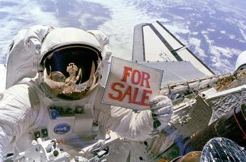 "US Space Shuttle Astronaut Dale A. Gardner, having just completed the major portion of his second extravehicular activity (EVA) period in three days, holds up a ""For Sale"" sign refering to the two satellites, Palapa B-2 and Westar 6"