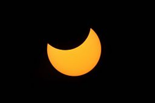 The crescent shape of a partial solar eclipse is caused when the moon enters the path between the earth and sun.