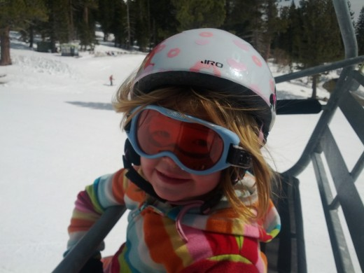 Four year old girl riding the ski lift up the mountain at Alpine Village Ski Resort in Lake Tahoe.