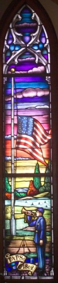 A stained glass window depicting a bugler playing Taps.