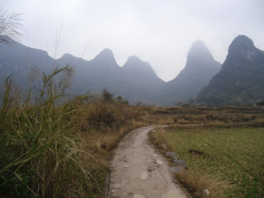 A muddy path somewhere outside of Yangshuo with karst mountains surrounding.