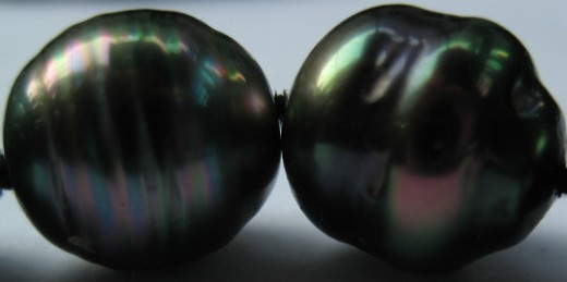 Detailed photograph of two peacock Tahitian pearls in a necklace, showing the silk knot between the pearls. (c)  A. Jones 2012