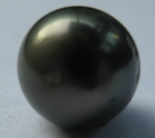 This single, round dark grey Tahitian pearl is smooth, and has good (but not amazing) lustre. The overtones are a muted dark green.  (c) A Jones 2012