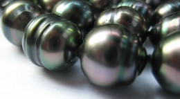 A close-up picture of a few of a necklace of baroque peacock Tahitian pearls. The lustre and colour on these are wonderful, and the surface smooth with a few pits. They are approximately 9 to 10mm in size.  (c) A Jones 2012