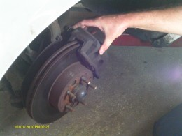 Remove the caliper to get to the brake pads, and inspect for damage.  Replace as necessary.