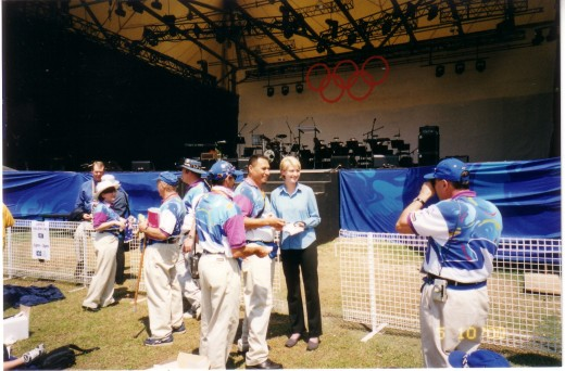Tara Brown Tv presenter being photographed with Sydney 2000 Driver Volunteers. DRivers had purple colered flashing to their polo tops