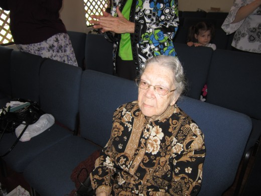 91 year old woman praying and attending church service.