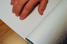 Hand reading a Braille book.