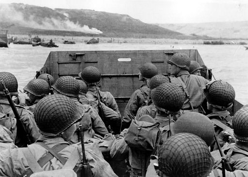 """Troops in an LCVP landing craft approaching """"Omaha"""" Beach on """"D-Day"""", 6 June 1944. Note helmet netting; faint """"No Smoking"""" sign on the LCVP's ramp; and M1903 rifles and M1 carbines carried by some of these men."""
