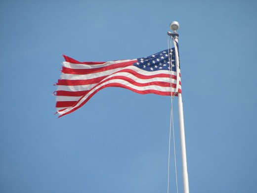 A waving American flag atop the United States Capitol Building.