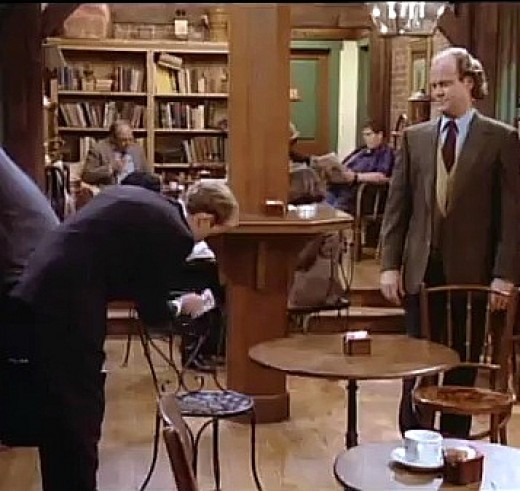 Frasier observes as his fastidious brother cleans a cafe chair.
