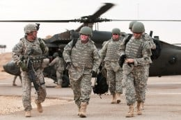 U.S. Army Command Sgt. Maj. Lawrence Wilson, left, accompanies Army Sgt. 1st Class Mike Schlitz, a wounded warrior returning to Iraq as part of Operation Proper Exit, on Camp Ramadi, Iraq, Dec. 29, 2009. The program returns severely wounded veterans