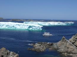 Tourist boat approaching huge iceberg.