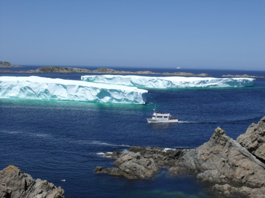 Tourist boat approaching huge iceberg.