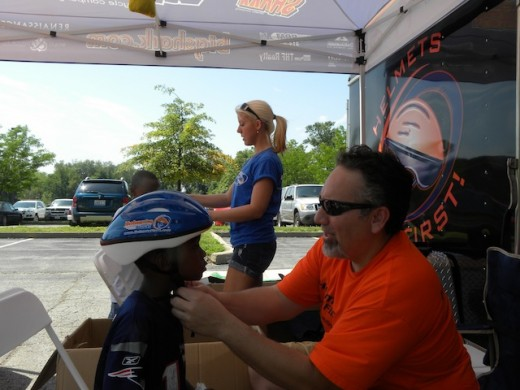 Pediatrician Dr. Joseph Cangas fits a bike helmet on a child during a Family Safety Fest in Alton, May 2012. Cangas has given away thousands of bike helmets to prevent head injuries in kids.