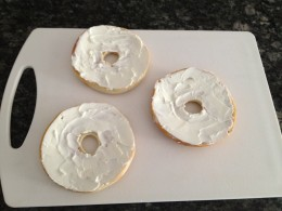 Cover tops of bagels completely with cream cheese.