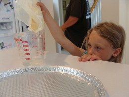 Grace carefully watches to see how much she needs to pour into the measuring cup.