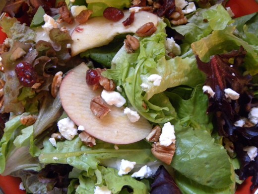 Sweet Salad with Balsamic Fig Dressing. You can see the bits of feta cheese, nuts, fruit and cranberries sprinkled over the fresh spring greens.