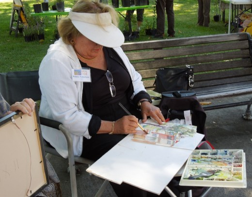 Kaaren Robertson works on her plein air painting to enter in the Quick Draw event. What she is working on will be auctioned off in a couple of hours.
