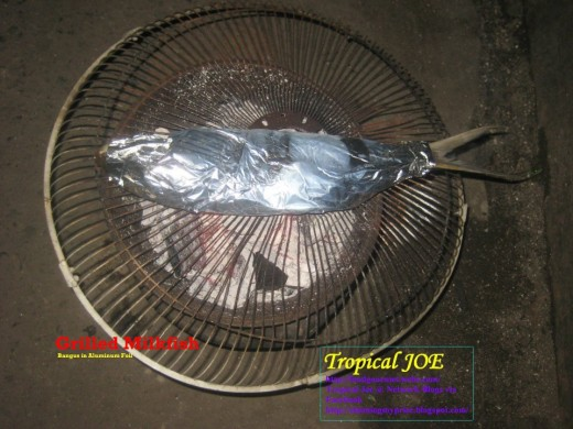 Grilled Milkfish - or bangus, warpped in aluminum foil, filling consists of spices (onion, garlic, pepper, tomatoes, salt, lemon or vinegar and  ground black pepper)