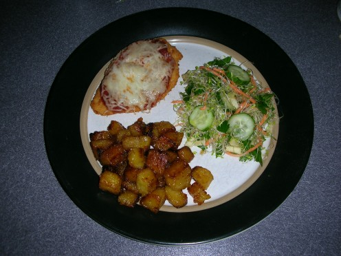 Plated chicken parmesan with plantains and salad
