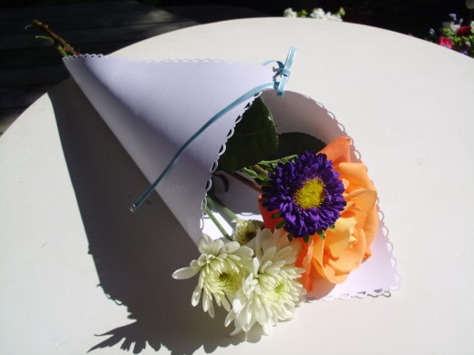 Decorated Paper Wrap for floral arrangement wedding favor for guests. Flowers are from Village Gardens in Blue Springs, Missouri.