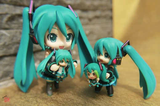 "A ""family"" of Nendoroids. To the left we have a regular Nendoroid holding a Nendoroid Petit Plus. To the right we have a Nendoroid Petit holding a different Nendoroid Petit Plus. All of these figures are variations of the virtual singer Hatsune Miku."