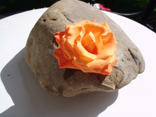 Zen Rock Wedding Table Décor. River rock and single, very open flowers