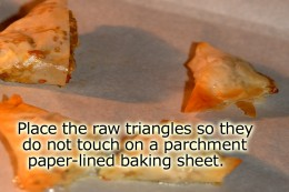 Place the raw stuffed triangles on a baking sheet that is lined with parchment paper. Make sure they do not touch.
