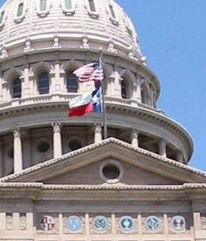 The Texas flag flying below the U.S. flag at the Texas State Capitol