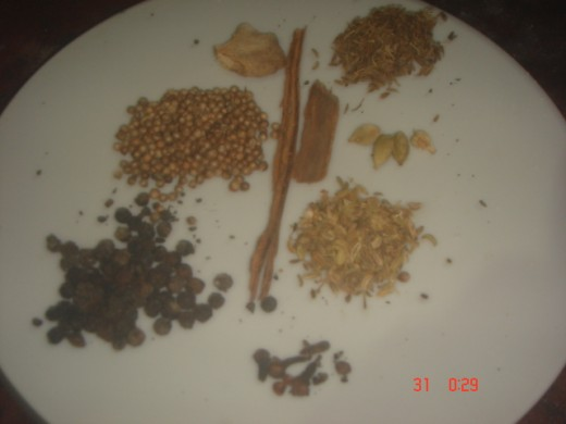 Whole spices.top right clockwise. cumin seeds, cardamom, fennel seeds, cloves, pepper corns, coriander seeds, dry ginger.