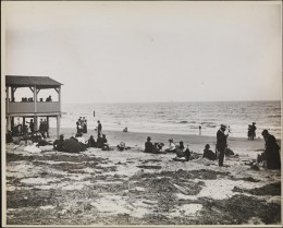 Title: On the Beach in Coney Island Date: 1895 Comments: View of people on the beach at Coney Island.  A pavilion is visible to the left.